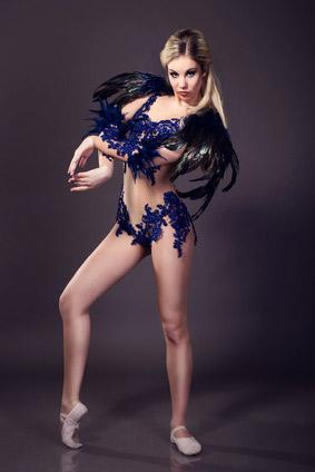 Ballerina im Black Swan Kostüm posiert vor neutralem Hintergrund