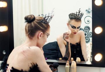 Ballerina vor einem Spiegel am Anfang des Black Swan Make-ups