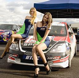 Russische Fraun sitzen mit Boxenluder Kostümen auf einem Rallye Auto