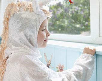 Ein Kind im Einhorn Kostüm schaut aus dem Fenster
