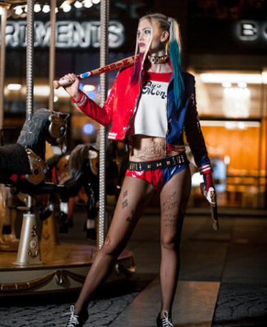 Harley Quinn Kostüm in Lack- und Lederoptik am Abend vor einem Karussell