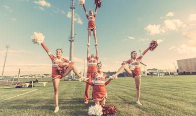 Sportliche Cheerleader führen eine schwierige Stellung auf dem Rasen vor