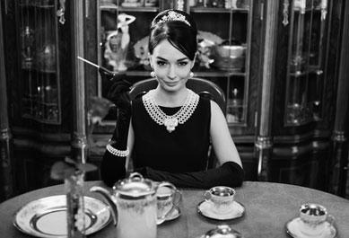 Eine Dame im Audrey Hepburn Kostüm an einem Tisch - Schwarz-weiß