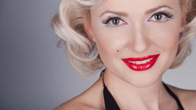 Junge Dame im Marilyn Monroe Kostüm inklusive Perücke auf neutralem Hintergrund