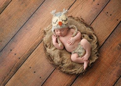 Baby im Eulenkostüm und Eulennest