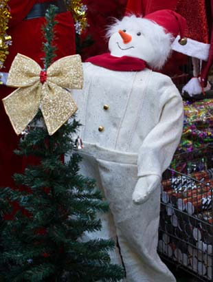 Schneemann Kostüm neben Tannenbaum